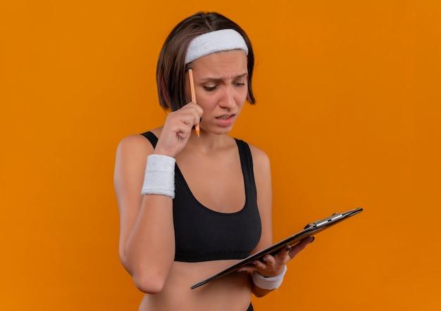 Junge fitnessfrau in der sportbekleidung mit dem stirnband, das klemmbrett mit leeren seiten kratzt kopf mit einem stift, der verwirrt steht über orange wand steht