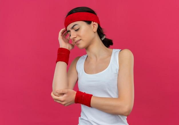Junge fitnessfrau in der sportbekleidung mit dem stirnband, das unwohl schaut, das ihren ellbogen berührt, der schmerzen hat, die über rosa wand stehen