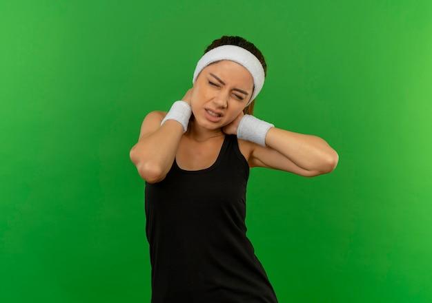 Junge fitnessfrau in der sportbekleidung mit dem stirnband, das unwohl schaut, das ihren nacken berührt, der schmerzen hat, die über grüner wand stehen