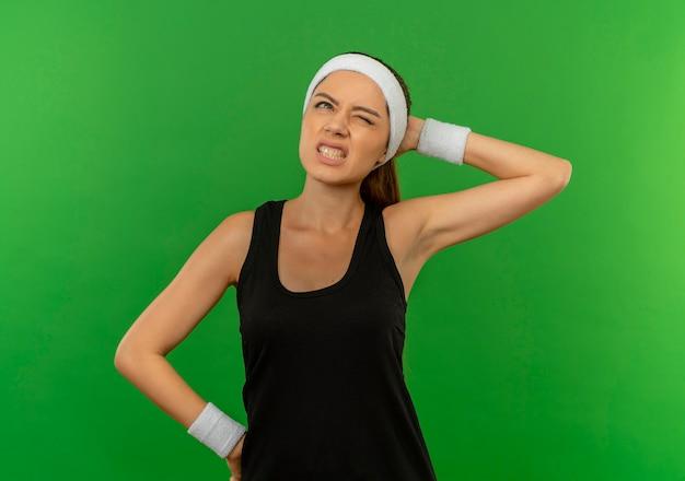 Junge fitnessfrau in der sportbekleidung mit dem stirnband, das verwirrt schaut, das ihren kopf für fehler steht, der über grüner wand steht