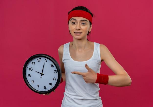 Junge fitnessfrau in der sportbekleidung mit dem stirnband, das wanduhr hält, zeigt mit dem finger, der verwirrt steht über rosa wand