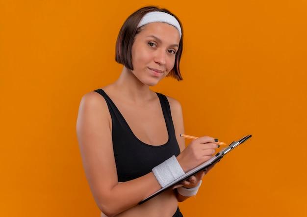 Junge fitnessfrau in der sportbekleidung mit dem stirnband, das zwischenablage mit leeren seiten hält, die sicher schauen über orange wand stehen