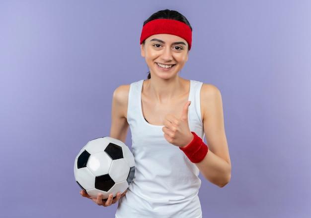 Junge fitnessfrau in der sportbekleidung mit dem stirnband, der fußball lächelnd zuversichtlich zeigt, zeigt daumen hoch, die über lila wand stehen