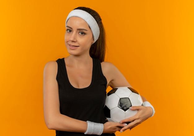 Junge fitnessfrau in der sportbekleidung mit dem stirnband, der fußball schaut, der zuversichtlich steht über orange wand