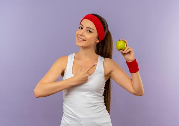Junge fitnessfrau in der sportbekleidung mit dem stirnband, der grünen apfel hält, der mit dem finger auf ihn lächelt, der zuversichtlich über graue wand steht