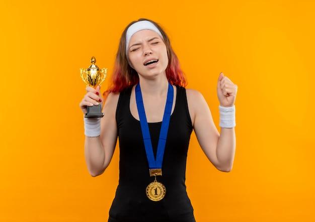 Junge fitnessfrau in der sportbekleidung mit goldmedaille um ihren hals, der fäuste anhebt, die trophäe mit genervtem ausdruck über orange wand stehen