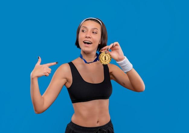 Junge fitnessfrau in der sportbekleidung mit goldmedaille um ihren hals, die medaille zeigt mit zeigefinger darauf lächelnd zuversichtlich mit stolzem stehen über blauer wand