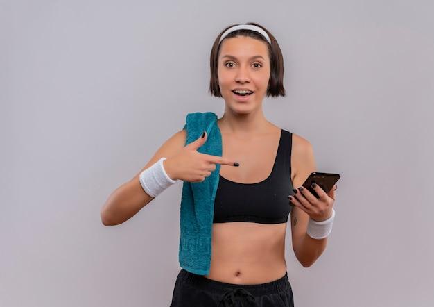 Junge fitnessfrau in der sportbekleidung mit handtuch auf der schulter, die das smartphone zeigt, das mit dem finger zeigt, der über weißer wand lächelnd steht