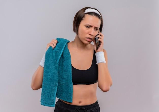 Junge fitnessfrau in der sportbekleidung mit handtuch auf der schulter, die verwirrt und ängstlich schaut, während auf handy steht, das über weißer wand steht