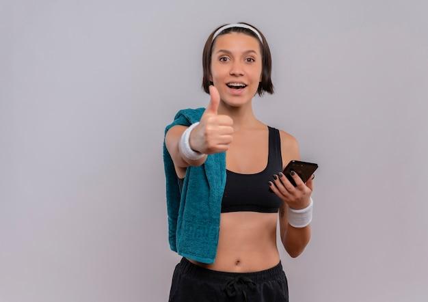 Junge fitnessfrau in der sportbekleidung mit handtuch auf schulter, die das lächelnde smartphone hält, zeigt daumen hoch, die über weiße wand stehen