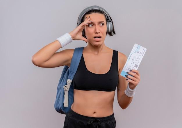 Junge fitnessfrau in der sportbekleidung mit kopfhörern auf kopf mit rucksack, der das flugticket hält, das beiseite schaut, verwechselt mit dem angstausdruck, der über weißer wand steht
