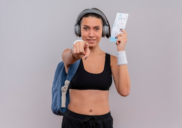 Junge fitnessfrau in der sportbekleidung mit kopfhörern auf kopf mit rucksack, der flugschein hält, zeigt mit dem finger auf kamera lächelnd über weiße wand stehend
