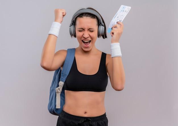 Junge fitnessfrau in der sportbekleidung mit kopfhörern auf kopf mit rucksack, der luftticket ballt, die faust ballen