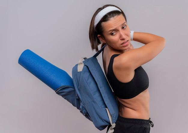 Junge fitnessfrau in der sportbekleidung mit rucksack und yogamatte, die unzufrieden und verwirrt beiseite steht, die über weißer wand stehen