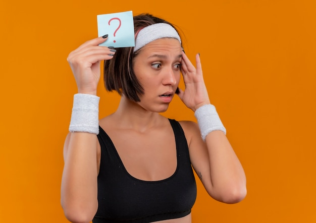 Junge fitnessfrau in der sportbekleidung mit stirnband, die erinnerungspapier mit fragezeichen hält, das beiseite überrascht überrascht steht über orange wand
