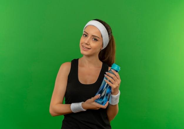 Junge fitnessfrau in der sportbekleidung mit stirnband, die flasche des wassers hält, das zuversichtlich steht, über grüner wand steht