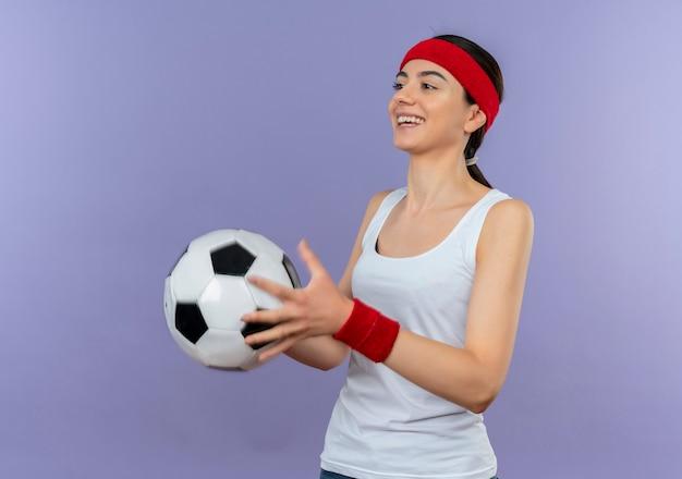 Junge fitnessfrau in der sportbekleidung mit stirnband, die fußball lächelnd zuversichtlich glücklich und positiv steht über lila wand