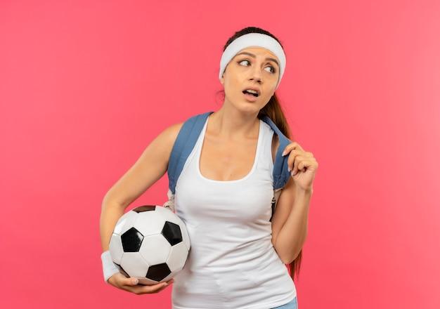 Junge fitnessfrau in der sportbekleidung mit stirnband und goldmedaille um ihren hals mit rucksack, der fußball hält, der beiseite steht, verwirrt über rosa wand steht