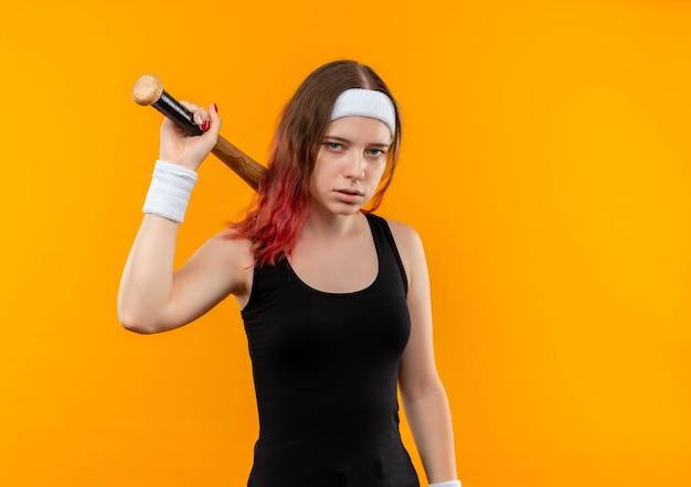 Junge fitnessfrau in der sportkleidung, die baseballschläger mit ernstem gesicht hält, das über orange wand steht