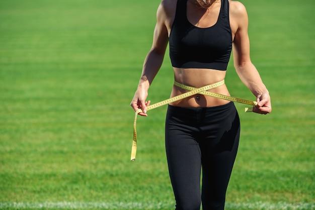 Junge fitnessfrau in schwarzer sportbekleidung mit perfekter taille mit einem maßband in den händen