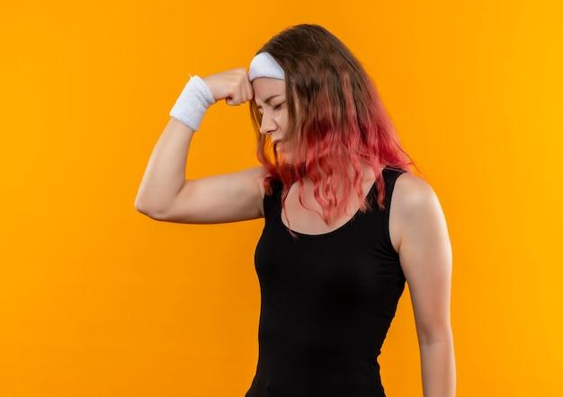 Junge fitnessfrau in sportbekleidung, die verwirrten berührenden kopf für fehler sucht