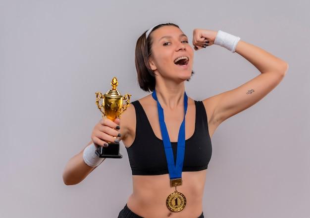Junge fitnessfrau in sportbekleidung mit goldmedaille um den hals hält ihre trophäe, die die faust hebt, glücklich und aufgeregt und freut sich über ihren erfolg, der über weißer wand steht