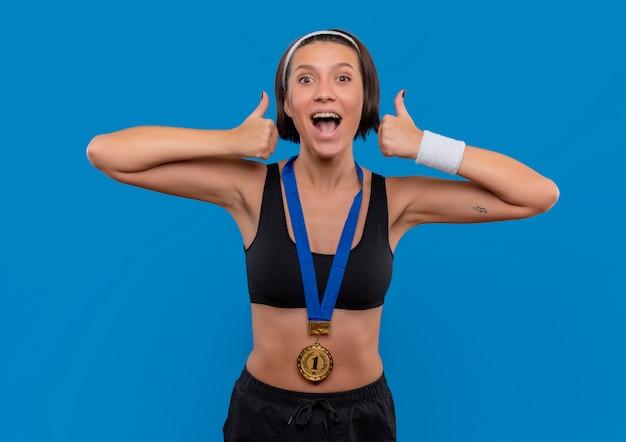 Junge fitnessfrau in sportbekleidung mit goldmedaille um den hals zeigt daumen hoch und freut sich über ihren erfolg, glücklich und aufgeregt über der blauen wand stehend