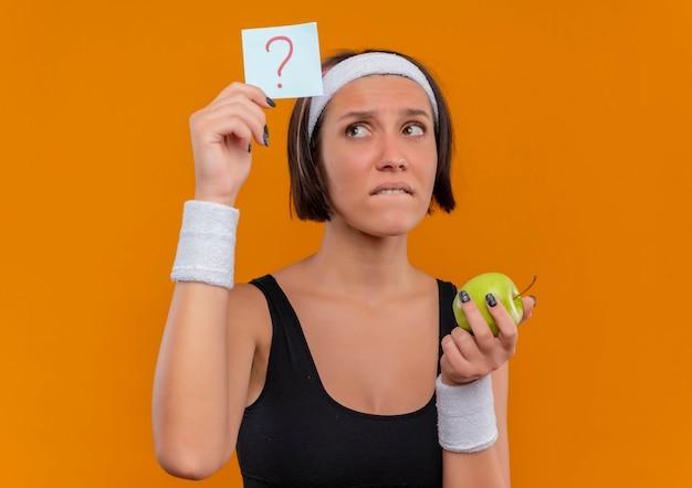 Junge fitnessfrau in sportbekleidung mit stirnband, das erinnerungspapier mit fragezeichen hält, das grünen apfel betrachtet, der papier verwirrt über orange wand steht