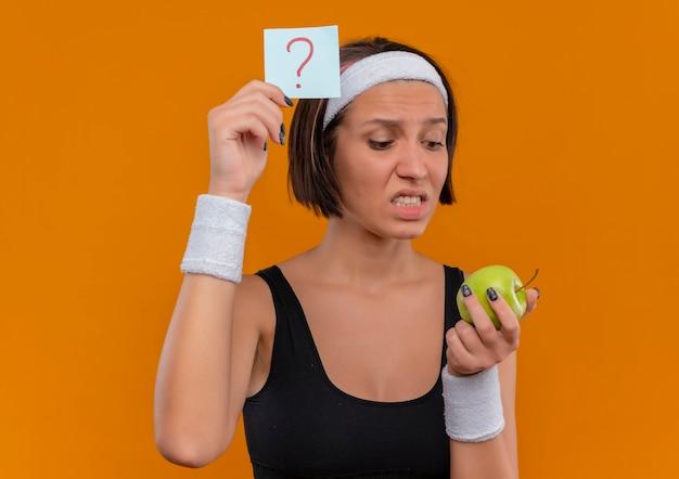 Junge fitnessfrau in sportbekleidung mit stirnband, das erinnerungspapier mit fragezeichen hält, das grünen apfel hält, der es verwirrt und sehr ängstlich betrachtet, über orange wand steht