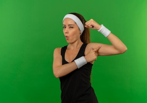 Junge fitnessfrau in sportbekleidung mit stirnband, das faust anhebt, die ihren bizeps zeigt, der zuversichtlich zwinkert, über grüne wand stehend