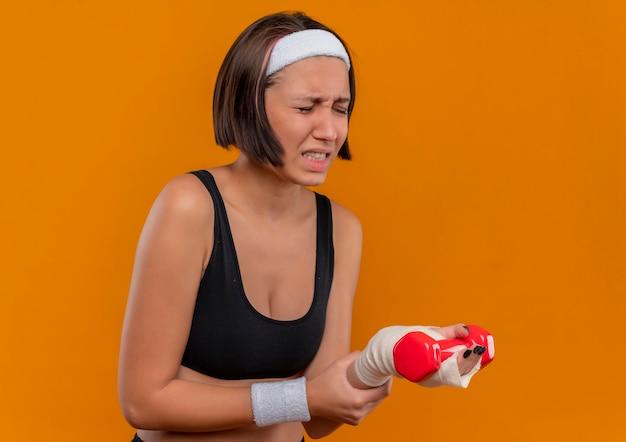 Junge fitnessfrau in sportbekleidung mit stirnband, das hantel hält, die ihr handgelenk berührt, das unwohl fühlt, das schmerz steht über orange wand