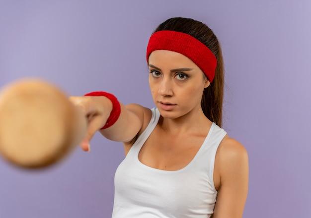 Junge fitnessfrau in sportbekleidung mit stirnband, das mit baseballschläger zur kamera mit ernstem gesicht zeigt, das über graue wand steht