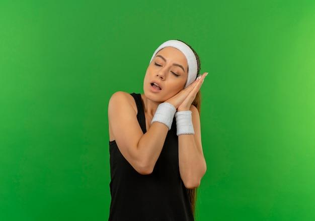 Junge fitnessfrau in sportbekleidung mit stirnband, das palmen zusammen mit geschlossenen augen hält, die kopf auf palmen lehnen, will über grüner wand stehen schlafen