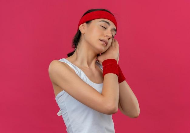 Junge fitnessfrau in sportbekleidung mit stirnband, das palmen zusammen mit geschlossenen augen hält, die kopf auf palmen lehnen, will über rosa wand stehen schlafen