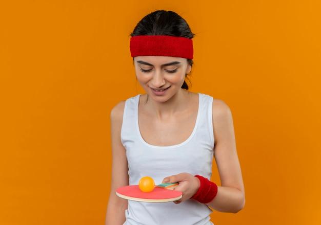 Junge fitnessfrau in sportbekleidung mit stirnband, das schläger und ball für tischtennis hält