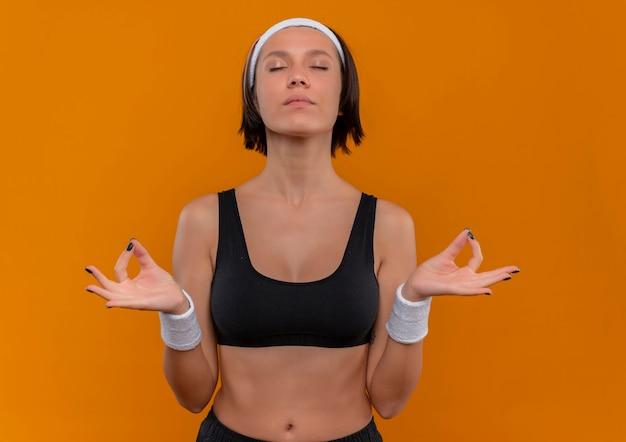 Junge fitnessfrau in sportbekleidung mit stirnband, das sich mit geschlossenen augen entspannt, meditationsgesten mit den fingern stehend über orange wand macht