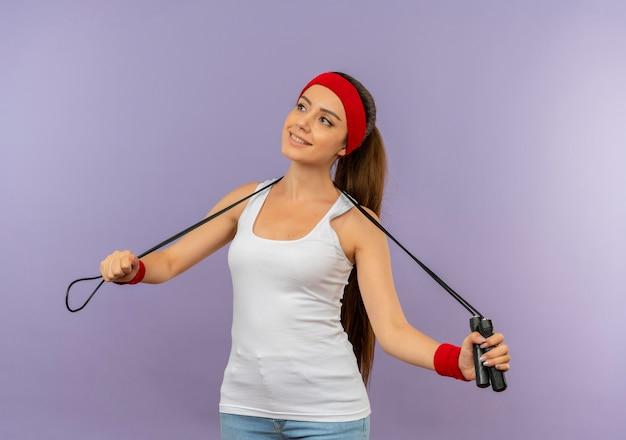 Junge fitnessfrau in sportbekleidung mit stirnband, das springseil glücklich und positiv lächelnd fröhlich über graue wand stehend hält