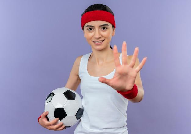 Junge fitnessfrau in sportbekleidung mit stirnband, die fußball hält stoppschild mit offener handfläche, die über lila wand steht