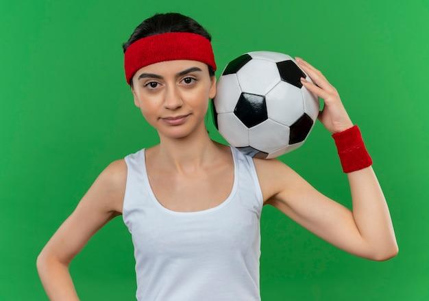 Junge fitnessfrau in sportbekleidung mit stirnband, die fußball mit dem sicheren ausdruck steht, der über grüner wand steht