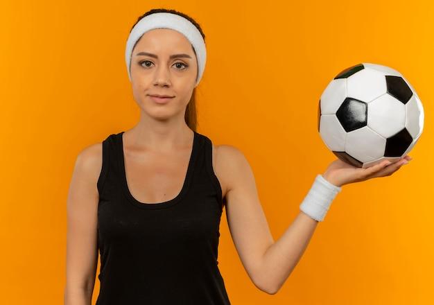 Junge fitnessfrau in sportbekleidung mit stirnband, die fußball mit ernstem gesicht hält, das über orange wand steht