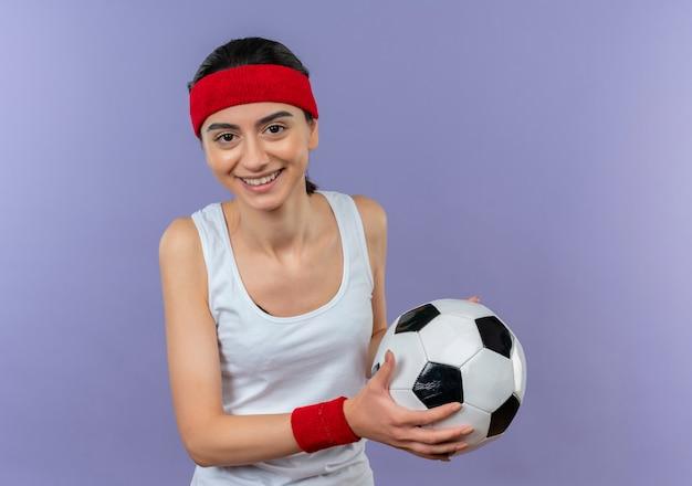 Junge fitnessfrau in sportbekleidung mit stirnband, die fußball mit lächeln auf gesicht steht, das über lila wand steht
