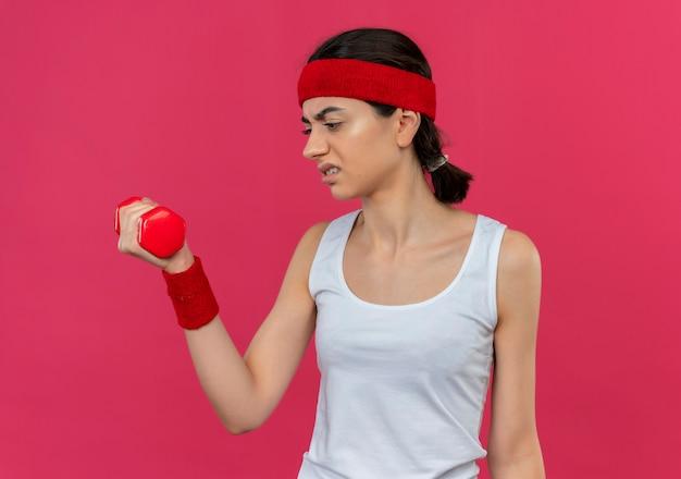 Junge fitnessfrau in sportbekleidung mit stirnband, die hantel in der erhöhten hand hält, die es mit genervtem ausdruck auf gesicht betrachtet, das über rosa wand steht