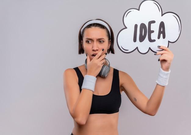 Junge fitnessfrau in sportbekleidung mit stirnband, die sprachblasenzeichen mit wortidee hält, die mit nachdenklichem ausdruck überrascht und erstaunt steht, der über weißer wand steht