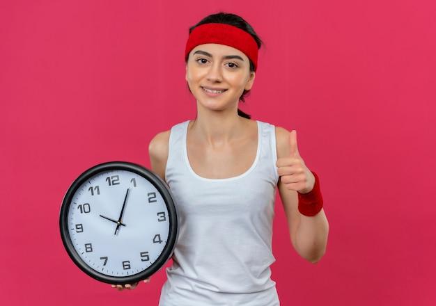 Junge fitnessfrau in sportbekleidung mit stirnband, die wanduhr lächelnd zeigt daumen hoch stehend über rosa wand