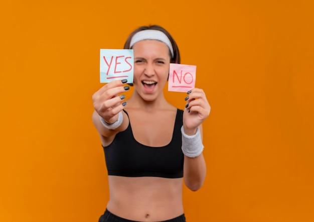 Junge fitnessfrau in sportbekleidung mit stirnband, die zwei erinnerungspapiere mit dem wort ja und nein zeigt, die fröhlich über orange wand stehend lächeln
