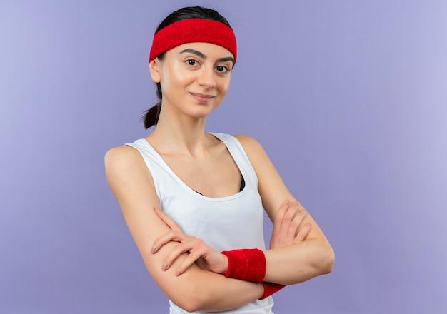 Junge fitnessfrau in sportbekleidung mit stirnband mit selbstbewusstem lächeln mit gekreuzten händen auf brust, die über lila wand steht