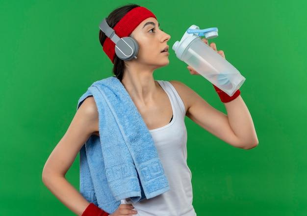 Junge fitnessfrau in sportbekleidung mit stirnband und handtuch auf ihrer schulter, die flasche wasser hält, das nach dem training steht, das über grüner wand steht