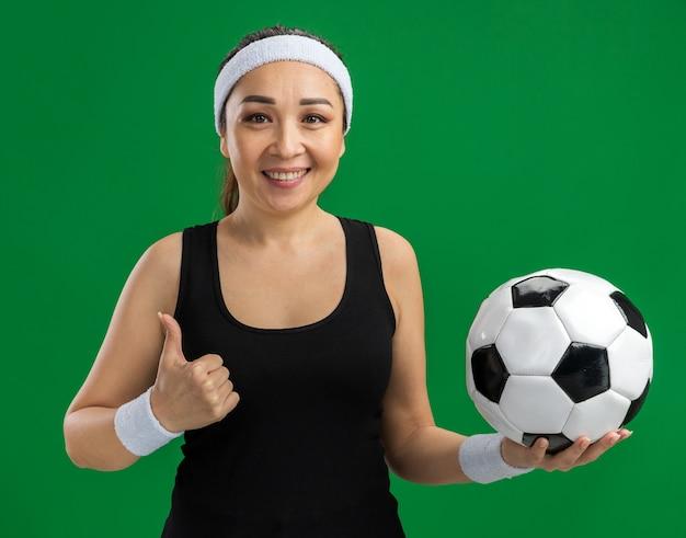 Junge fitnessfrau mit stirnband, die fußball mit einem lächeln auf dem gesicht hält, das über grüner wand steht