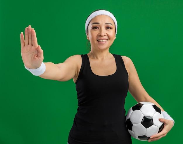 Junge fitnessfrau mit stirnband, die fußball mit einem lächeln im gesicht hält und eine stoppgeste mit offener hand über grüner wand macht