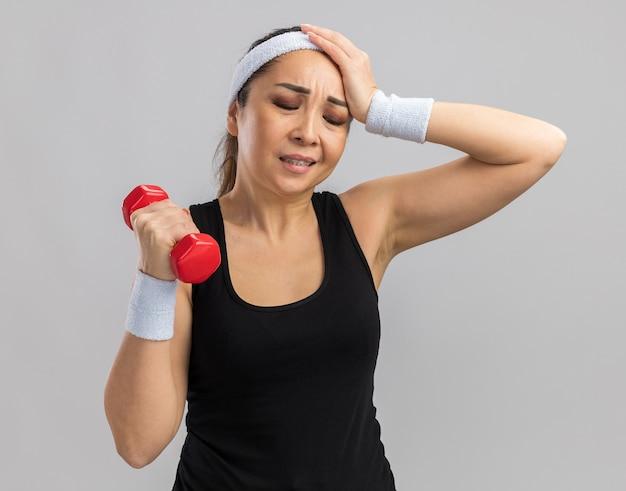 Junge fitnessfrau mit stirnband, die hantel hält und übungen macht, die mit der hand auf dem kopf für fehler verwirrt aussehen